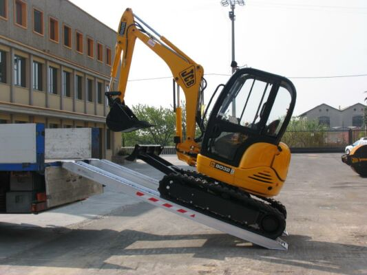 Mini digger loading on to tipper truck on ramps