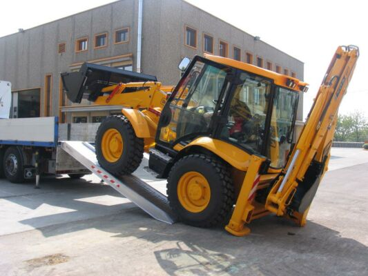 Digger loading on tipper truck using ramps
