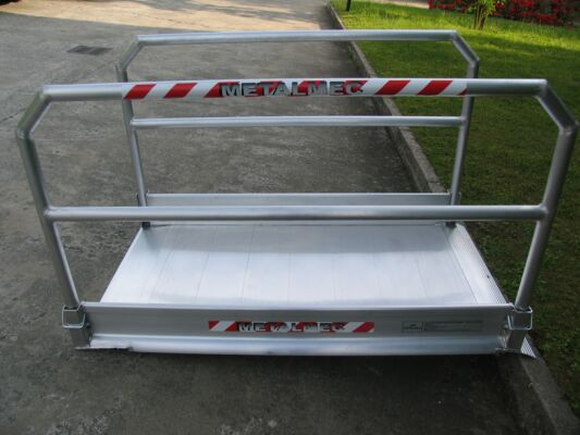 Vehicle ramp with grip surface and handrails