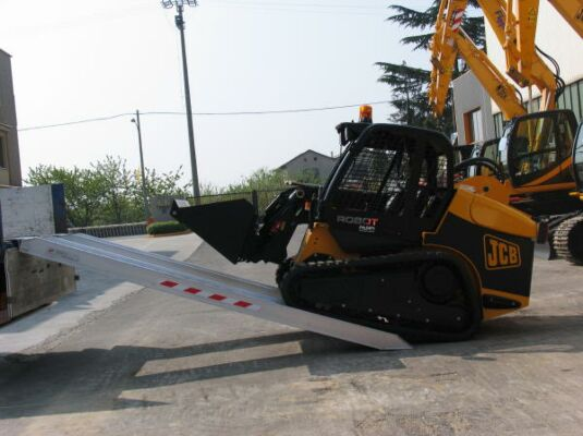 Loader driving on to loading ramps