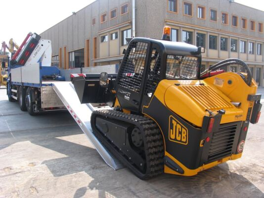 Skid steer loading driving on to loading ramps